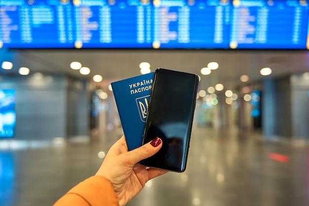 Паспорт и телефон в руке у информационного табло аэропорта