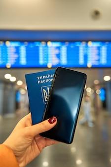 Паспорт и телефон в руке на фоне информационного табло аэропорта. путешествуйте с минимальным количеством вещей.