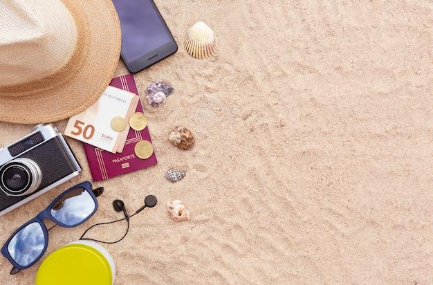 パスポートと現金、スマートフォン、帽子、カメラ、サングラスを砂の上に。フラットレイ