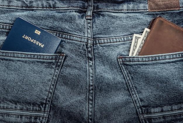 ジーンズの後ろポケットにドルが入ったパスポートと財布。旅行または移民の概念