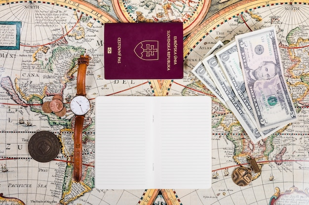 Passport, banknotes, wristwatch, coins and notepad on map