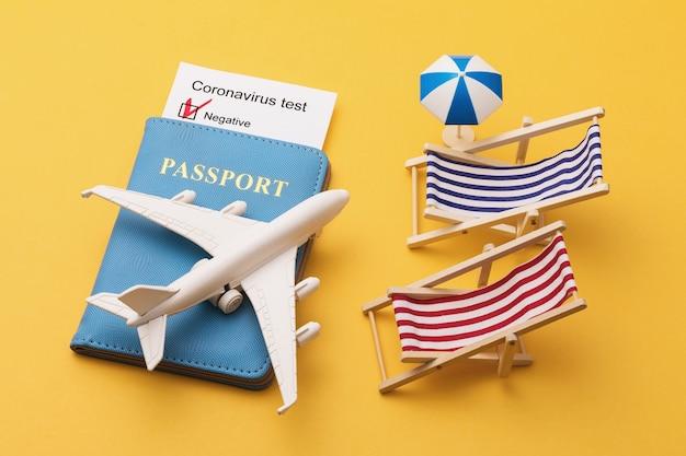 パスポートコロナウイルステスト結果黄色い表面のおもちゃの飛行機とサンラウンジャー