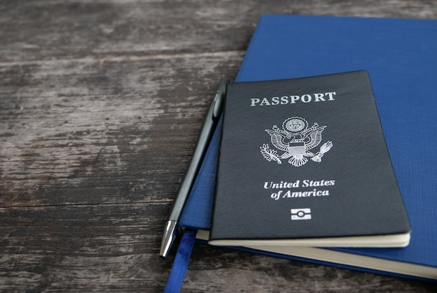 Passport diary notebook and pen with wooden background