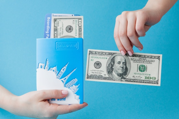 Passport, dollars and air ticket in woman hand on a blue background. travel concept, copy space