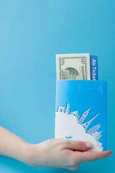 Passport, dollars and air ticket in woman hand on a blue surface. travel concept, copy space.