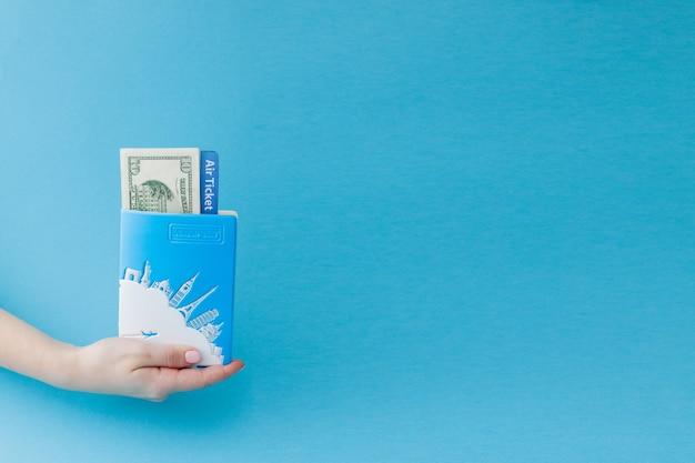 女性の手でパスポート、ドル、航空券