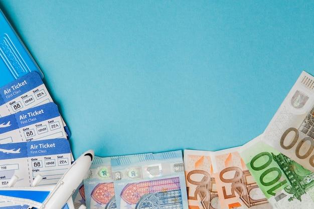 青色の背景にパスポート、ドル、ユーロ、飛行機、航空券。旅行の概念、コピースペース