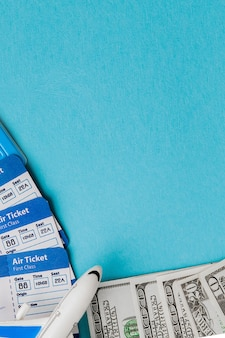 Passport, dollars, plane and air ticket on a blue background. travel concept, copy space