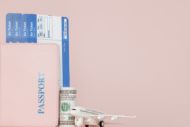 Passport, dollars, plane and air ticket on a pink background. travel concept, copy space