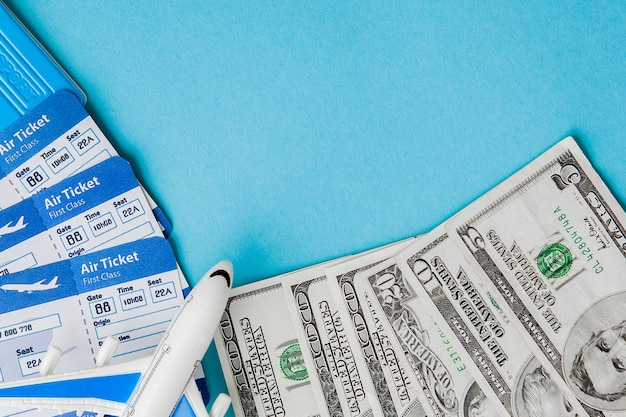 파란색 배경에 여권, 달러, 비행기 및 항공 티켓. 여행 개념, 복사 공간.