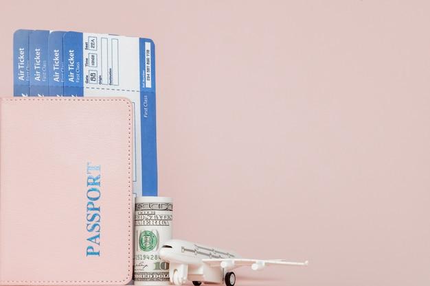 ピンクの背景のパスポート、ドル、飛行機、航空券。旅行の概念、コピースペース
