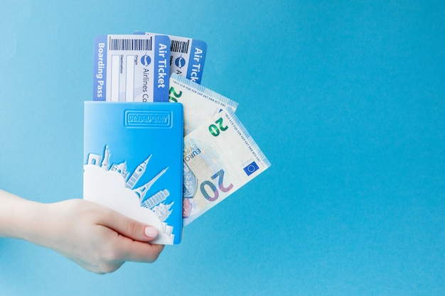 Passport, euro and air ticket in woman hand on a blue background