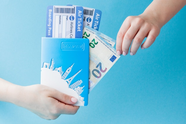 Passport, euro and air ticket in woman hand on a blue . travel , copy