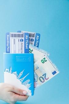 여자 손에 여권, 유로 및 항공 티켓. 여행 컨셉, 복사 공간