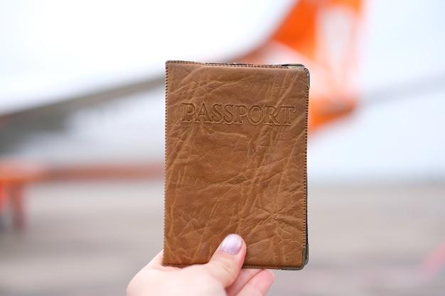 공항에서 비행기 배경에 있는 손에 든 여권 고품질 사진