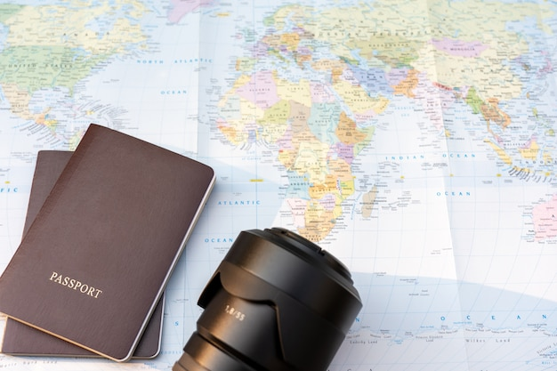 Passport and lens camera on a map of the world. globe map on a background.