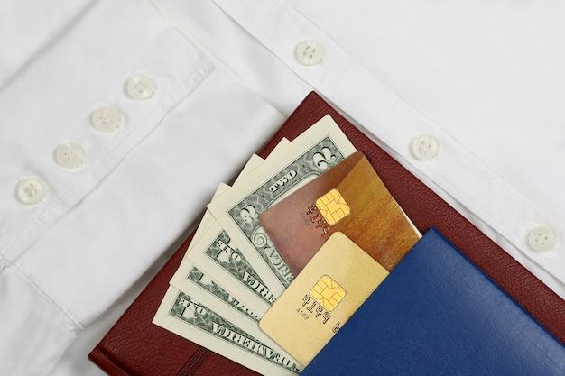 Паспорт, деньги и банковские карты на белой рубашке с рукавами