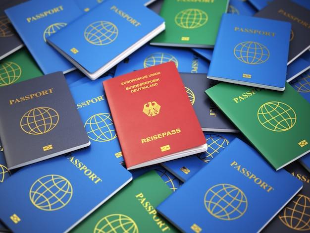 さまざまなパスポートの山にあるドイツのパスポート。移民の概念。 3d