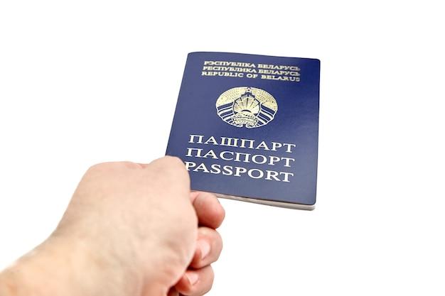 白い背景で隔離の手に青いカバーとベラルーシ共和国のパスポート