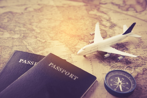 Passport, plane, compass placed on map -concept travel