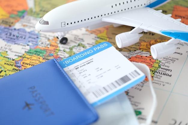 パスポートの飛行機のチケットとおもちゃの飛行機が世界地図上に立って、旅行のコンセプトのルートを選択します