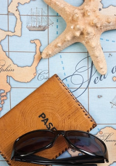 Passport and sunglasses on a map