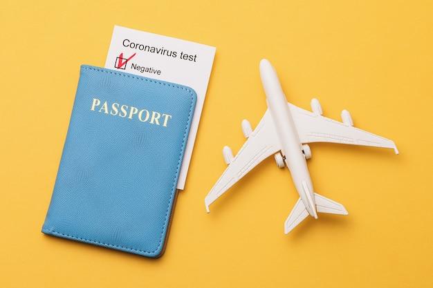 Паспорт отрицательного результата теста на коронавирус и игрушечный самолет на желтом фоне концепция разрешения авиаперелетов во время пандемии
