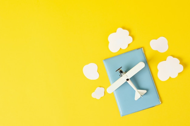 Passport, toy plane and decorative clouds on yellow, top view
