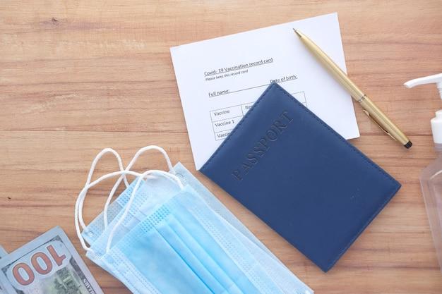 パスポート予防接種記録カード手指消毒剤とテーブル上のマスク
