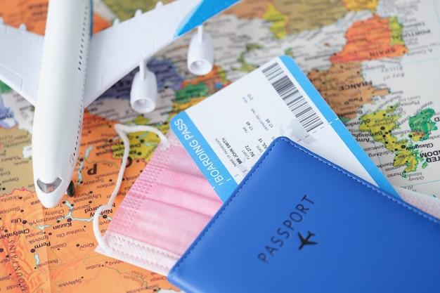 Паспорт с посадочным талоном и защитной медицинской маской, лежащий на карте мира с игрушечным самолетиком