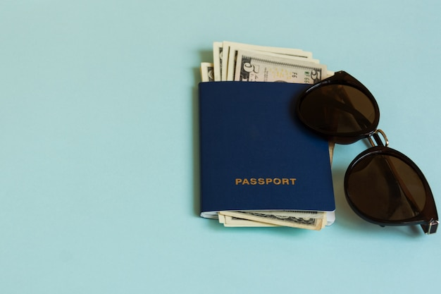 Passport with currency and sunglasses on pastel background