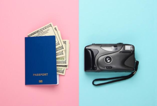 ドル札と青ピンクのパステルカラーのカメラ付きパスポート。フラットレイトラベルコンポジション。