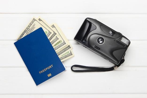 ドル札と白い木製のカメラ付きのパスポート。フラットレイトラベルコンポジション。