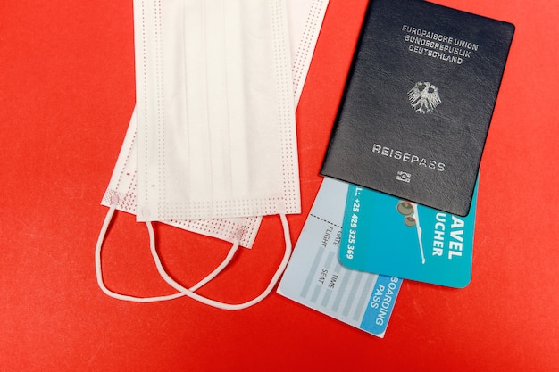 Passport with flight boarding pass and necessary hygiene face mask for aboard traveler to wear as healthcare measure to prevent disease infection or outbreak across country.