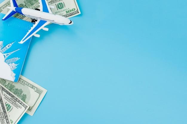 青い背景に旅客機とドルのモデルとパスポート。旅行のコンセプト、コピースペース。