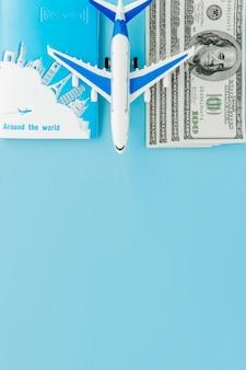 青の背景に旅客機とドルのモデルとパスポート。旅行のコンセプト