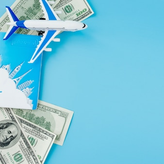 Passport with model of passenger plane and dollars on blue background. travel concept, copy space.