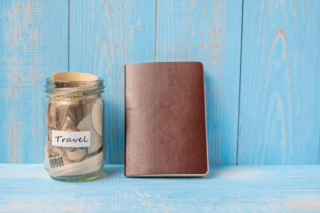 Passport with money banknote glass jar on blue wood