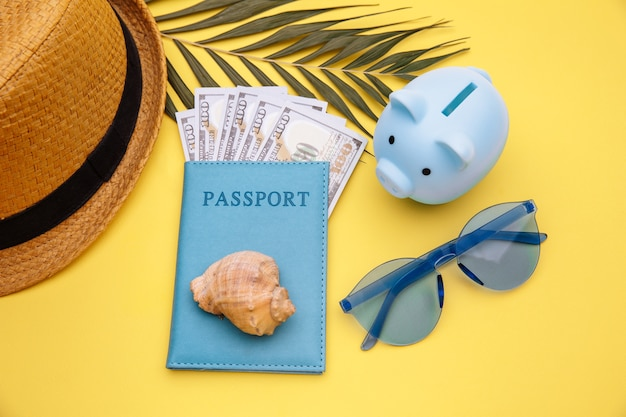 Passport with money and blue piggy bank on yellow table
