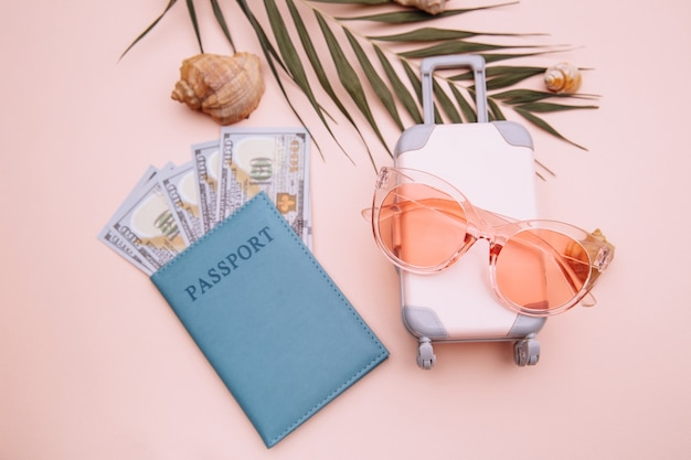 シェル付きのピンクの表面にお金、サングラス、ピンクのスーツケースが入ったパスポート。上面図。夏休み準備コンセプト