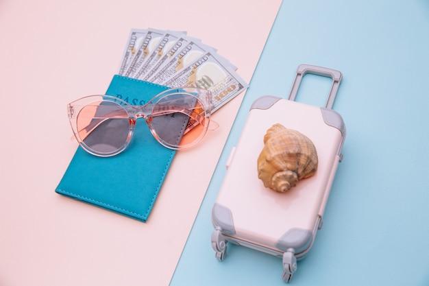 ピンクブルーの表面にシェル付きのお金、サングラス、スーツケースが入ったパスポート。旅行、夏休み、または観光の概念。