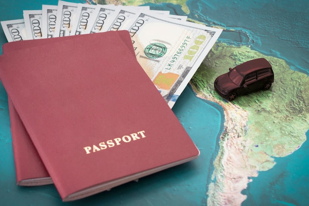 Passport with one hundred dollar bills inside and toy car on background of world map