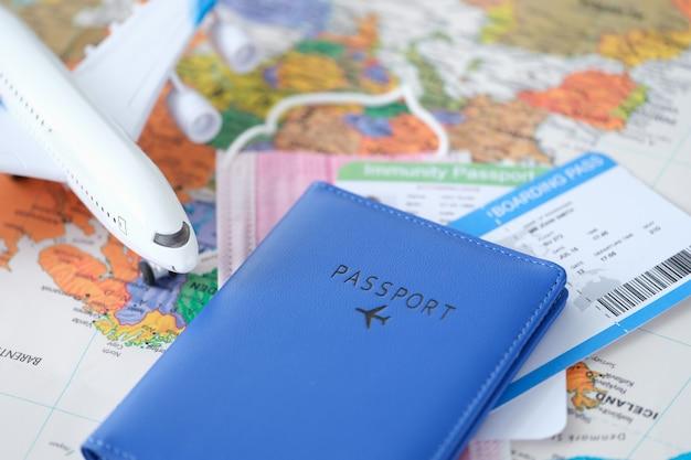 장난감 비행기 티켓과 코비드 예방 접종 증명서가 있는 여권은 세계 지도에 안전한 여행입니다