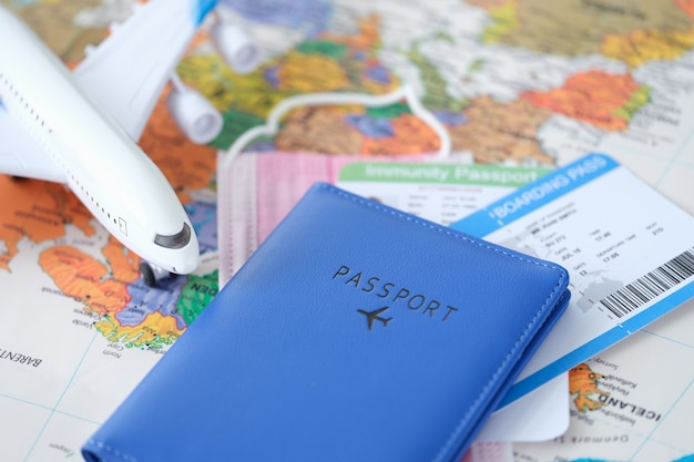 Passport with toy plane tickets and covid vaccination certificate are on world map safe travel