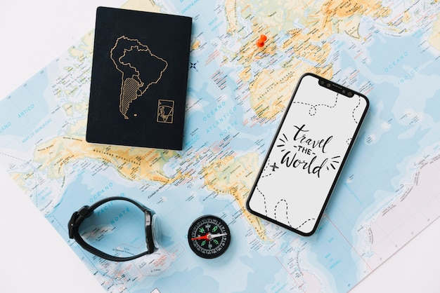 Passport; wrist watch; compass and mobile phone with travel message on white screen