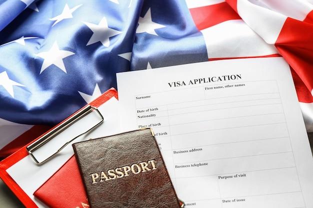 パスポート、アメリカ国旗、ビザ申請書がテーブルにあります。アメリカへの移民