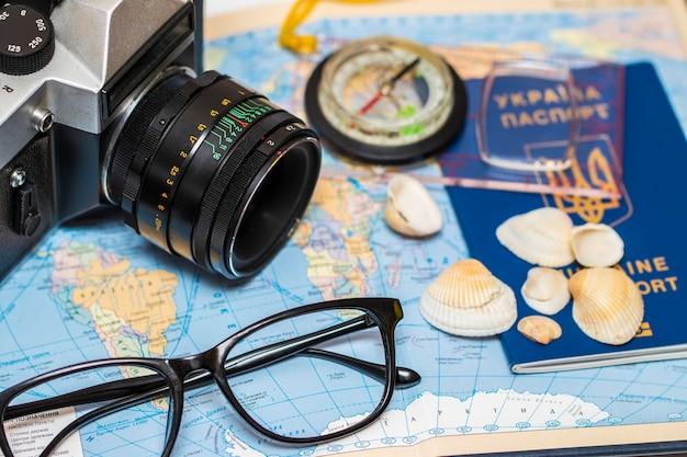 Паспорта на карте мира. камера, солнцезащитные очки и ракушки на заднем плане