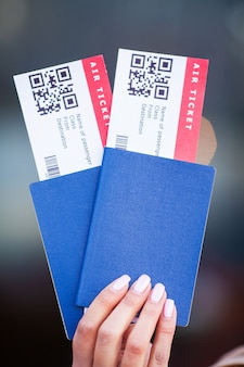 Passports and tickets for flight on hand of woman