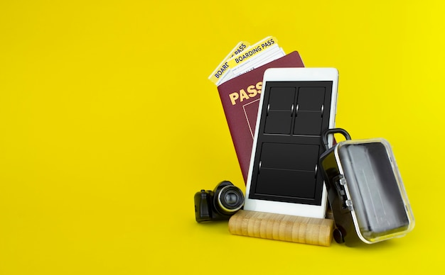Passports and tickets with suitcase on yellow background.