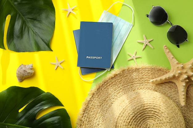 Passports with mask and vacation accessories on color isolated background